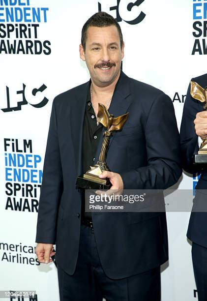 Adam Sandler poses in the press room with the Best Male Lead award for the film Uncut Gems during the 2020 Film Independent Spirit Awards on February...