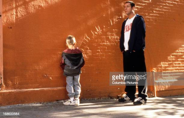 Adam Sandler standing with a child next to a orange painted brick wall in a scene from the film 'Big Daddy' 1999