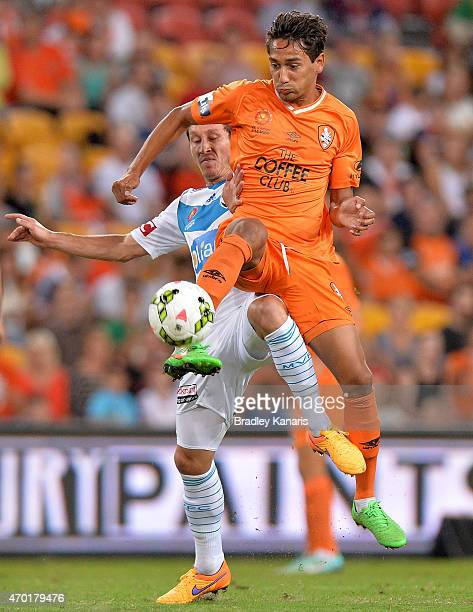Adam Sarota of the Roar and Mark Milligan of the Victory challenge for the ball during the round 26 ALeague match between the Brisbane Roar and...