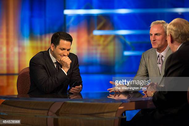 Adam Schefter left who has been an NFL Insider at ESPN for five years checks his cell phone between segments opposite Trey Wingo and Bill Polian on...