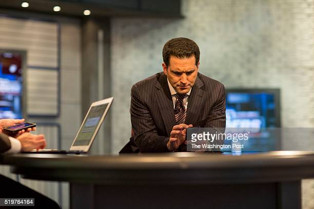 Adam Schefter who has been an NFL Insider at ESPN for five years checks his phone while on set for NFL Live at ESPN Headquarters just prior to...