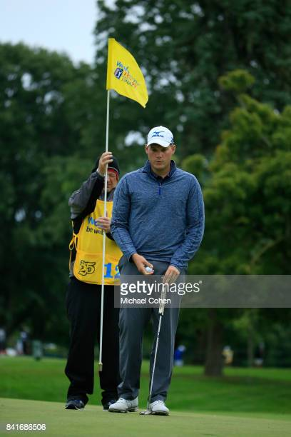 Adam Schenk prepares to putt on the 11th green as his caddie holds the flag during the second round of the Nationwide Children's Hospital...