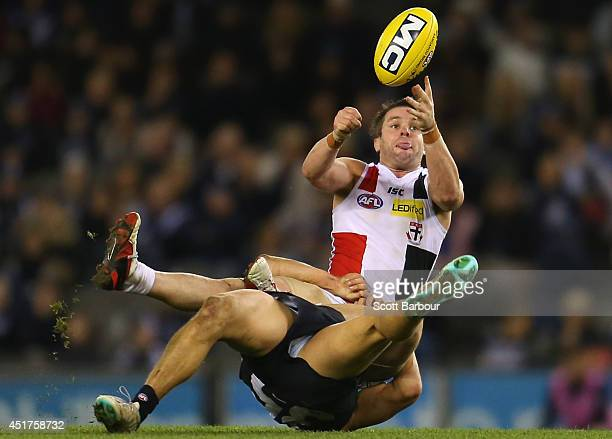 Adam Schneider of the Saints is tackled during the round 16 AFL match between the Carlton Blues and the St Kilda Saints at Etihad Stadium on July 6...