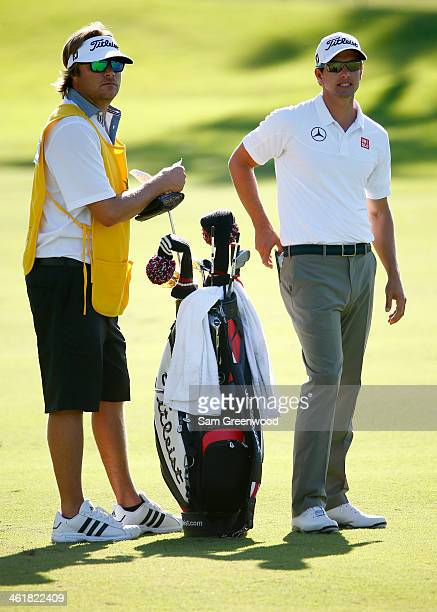 Adam Scott of Australia and professional surfer Benji Weatherley look over a shot on the 1st hole during the third round of the Sony Open in Hawaii...