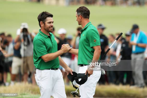 Adam Scott of Australia and the International team and Louis Oosthuizen of South Africa and the International team celebrate defeating Dustin Johnson...