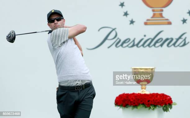 Adam Scott of Australia and the International Team plays his shot from the first tee during the Friday fourball matches during the second round of...