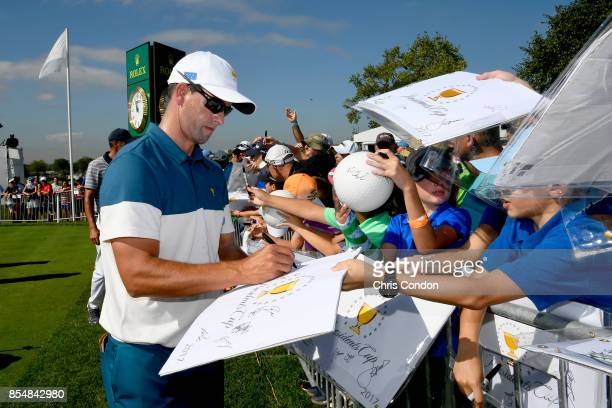 Adam Scott of Australia and the International Team signs his autograph for a fan prior to the start of the Presidents Cup at Liberty National Golf...