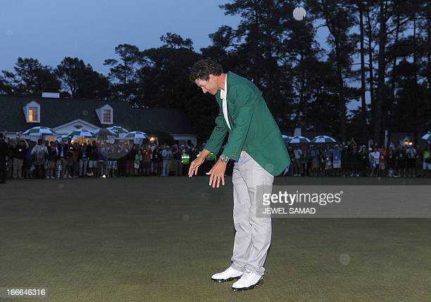 Adam Scott of Australia bows to the cheering crowd while wearing his green jacket after winning the 2013 Masters Tournament at Augusta National Golf...