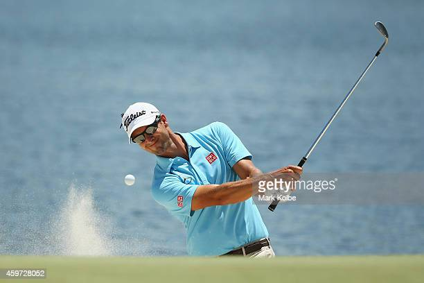 Adam Scott of Australia chips out of a bunker on the 4th hole during day four of the 2014 Australian Open at The Australian Golf Course on November...