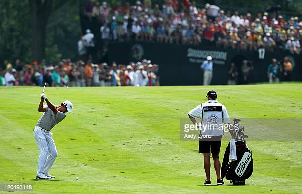 Adam Scott of Australia hits an approach shot on the 17th hole as caddie Steve Williams looks on during the third round of the World Golf...