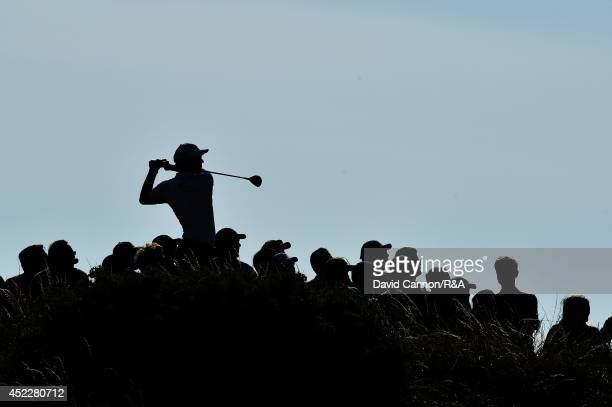 Adam Scott of Australia hits his tee shot on the 12th hole as a gallery of spectators look on during the first round of The 143rd Open Championship...