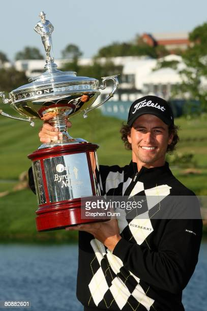 Adam Scott of Australia holds the trophy after his victory over Ryan Moore on the third playoff hole during the final round of the EDS Byron Nelson...
