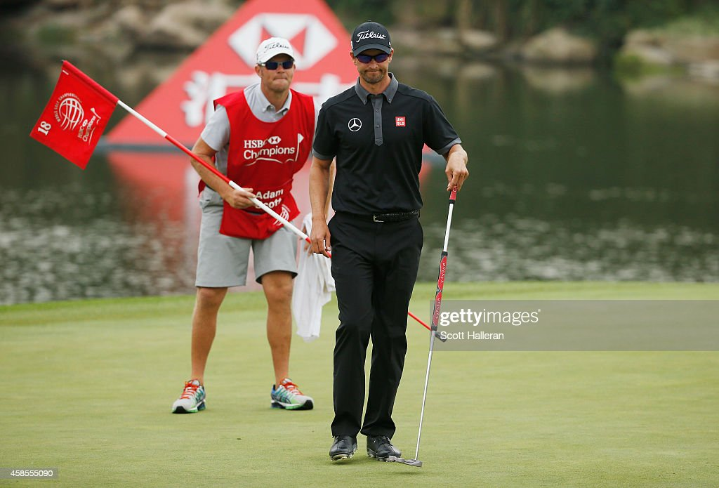 Adam Scott of Australia lines up a putt with his caddie David Clark on the 18th green during the second round of the WGC - HSBC Champions at the Sheshan International Golf Club on November 7, 2014 in Shanghai, China.