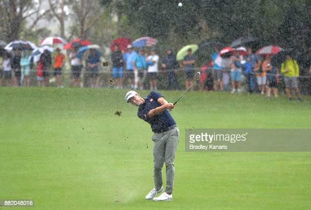 Adam Scott of Australia plays a shot as the rain falls during day one of the 2017 Australian PGA Championship at Royal Pines Resort on November 30...