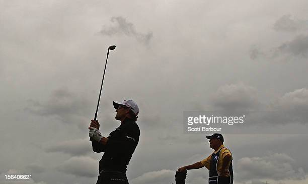 Adam Scott of Australia plays an approach shot as his caddie Steve Williams looks on during day one of the Australian Masters at Kingston Heath Golf...