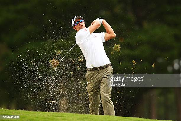 Adam Scott of Australia plays an approach shot on the 18th hole during day one of the 2014 Australian Open at The Australian Golf Course on November...