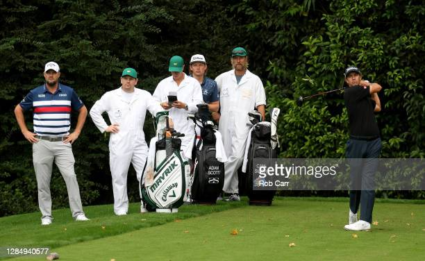 Adam Scott of Australia plays his shot from the 14th tee as Marc Leishman of Australia and Cameron Smith of Australia look on during a practice round...