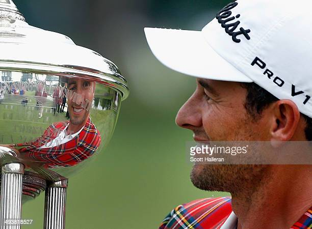 Adam Scott of Australia poses with the Leonard trophy after winning on a third playoff hole on the 18th hole during the Final Round of the Crowne...
