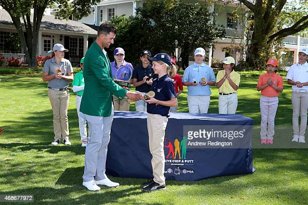 Adam Scott of Australia presents the trophy to Lydia Swan winner of the Girls 1011 division for the Drive Chip and Putt Championship at Augusta...