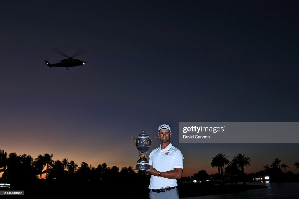 Adam Scott of Australia proudly holds the trophy as Donald Trump takes off in his helicopter after his one shot win in the final round of the 2016 World Golf Championship Cadillac Championship on the Blue Monster Course at the Trump National Doral Resort on March 6, 2016 in Doral, Florida.