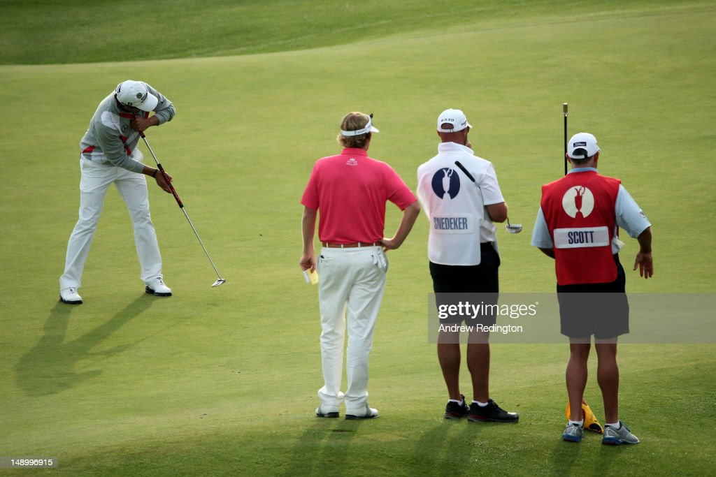 Adam Scott of Australia putts as Brandt Snedeker of the United States and caddies look on during the third round of the 141st Open Championship at Royal Lytham & St. Annes Golf Club on July 21, 2012 in Lytham St Annes, England.