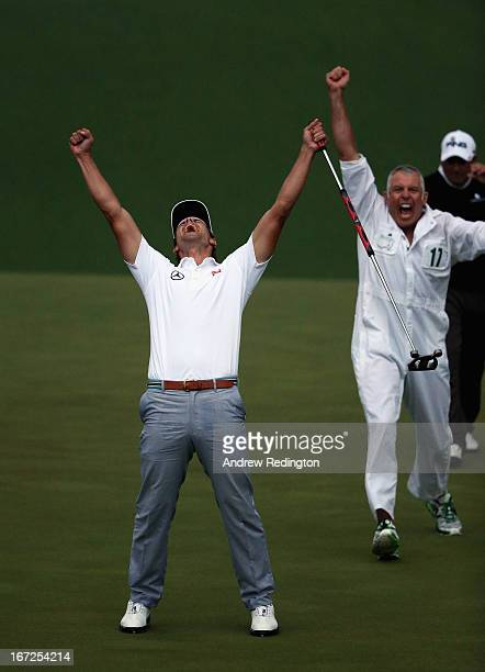 Adam Scott of Australia reacts alongside caddie Steve Williams after Scott makes a birdie putt on the second sudden death playoff hole to defeat...