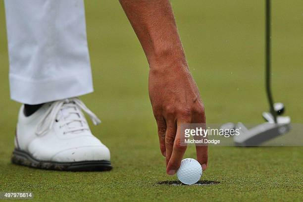 Adam Scott of Australia retrieves a ball after making a putt during day two of the 2015 Australian Masters at Huntingdale Golf Club on November 20...