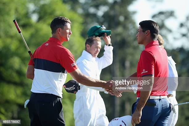 Adam Scott of Australia shakes hands with Jason Day of Australia on the 18th green after completing the third round of the 2015 Masters Tournament at...