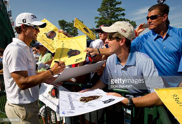 Adam Scott of Australia signs autographs near the 18th green during a practice round of the 2011 PGA Championship Tournament at Atlanta Athletic Club...