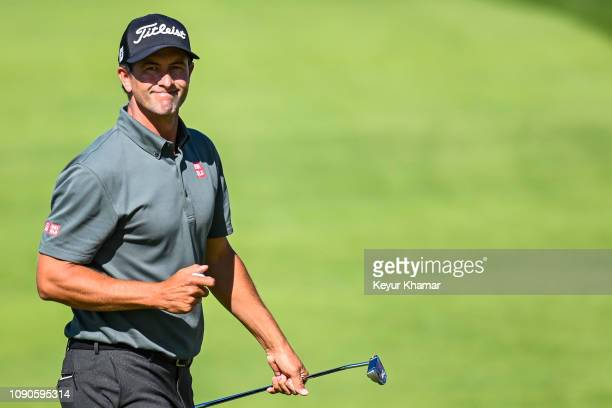 Adam Scott of Australia smiles after making a birdie putt on the ninth hole green during the final round of the Farmers Insurance Open on Torrey...
