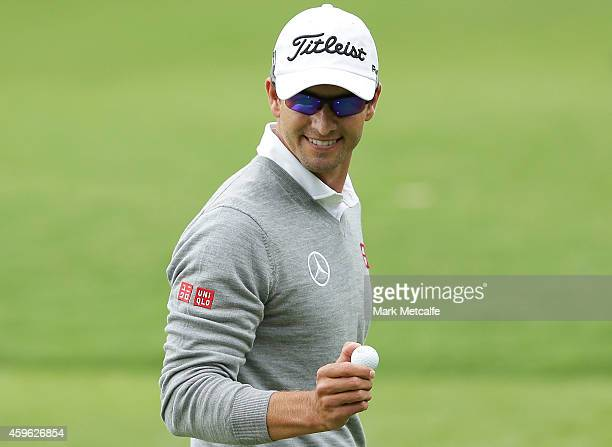 Adam Scott of Australia smiles as he talks to Jordan Spieth of the USA on the 1st hole during day one of the 2014 Australian Open at The Australian...