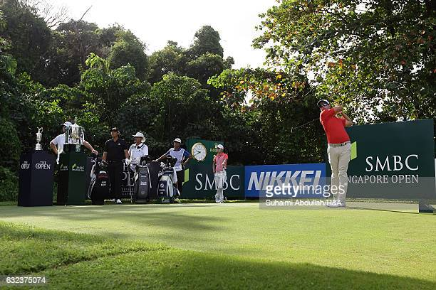 Adam Scott of Australia tees off on the first hole next to the SMBC Singapore Open trophy and the Claret Jug during day four of the SMBC Singapore...