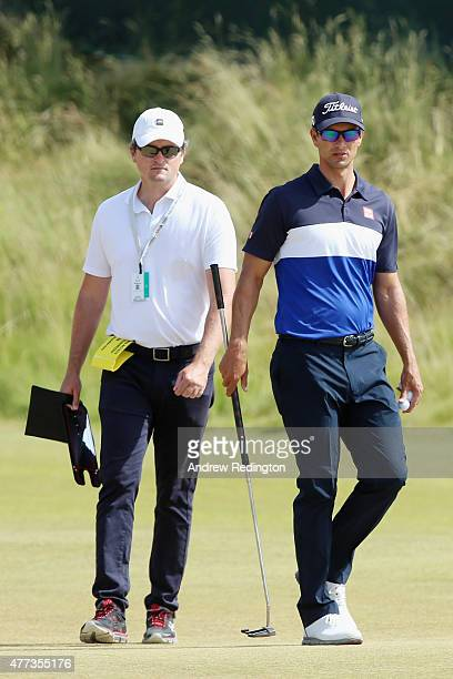 Adam Scott of Australia walks across a green with his swing coach and brother in law Brad Malone during a practice round prior to the start of the...