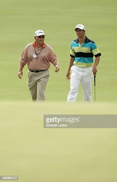 Adam Scott of Australia walks down the fairway with coach Butch Harmon during practice prior to the start of the US Open at Pinehurst Resort June 14...