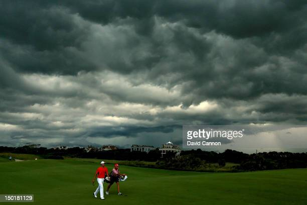 Adam Scott of Australia walks off the course under dark clouds as play is suspended due to a weather warning during Round Three of the 94th PGA...