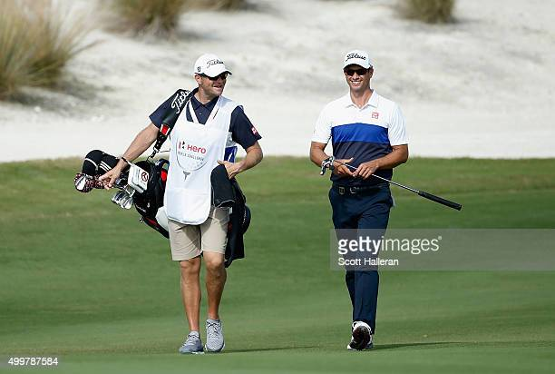 Adam Scott of Australia walks with his caddie David Clark to the first green during the first round of the Hero World Challenge at Albany The Bahamas...