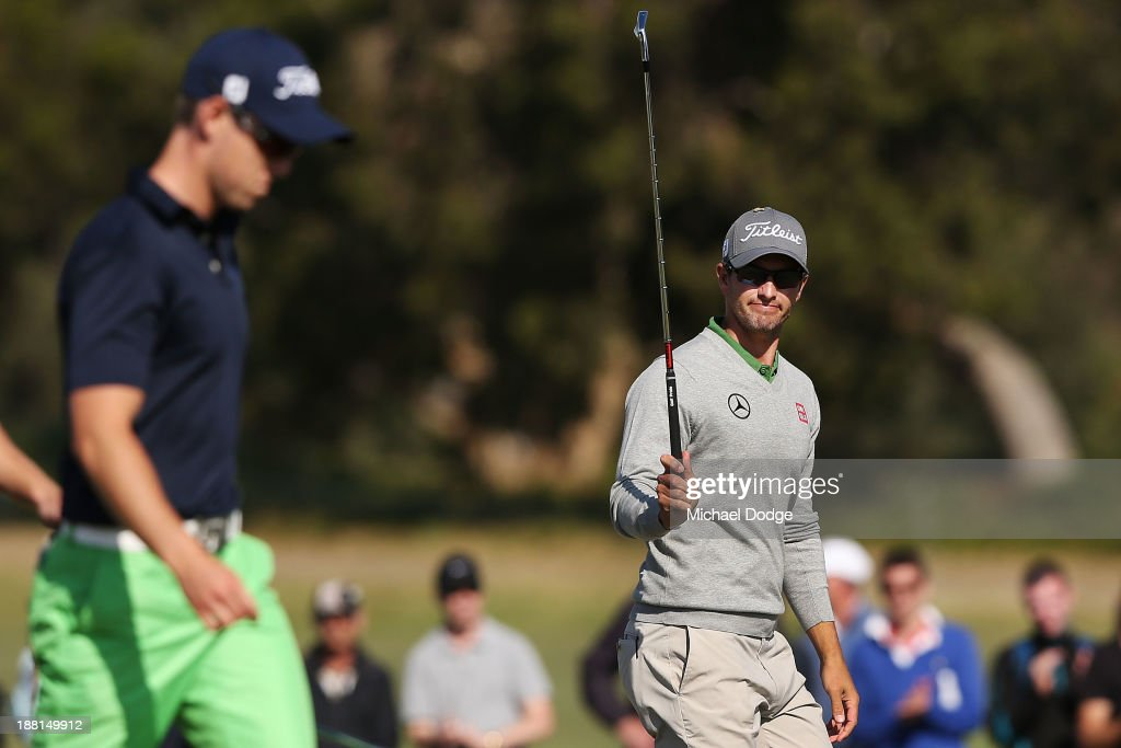 Adam Scott of Australia waves to the crowd next to Nathan Holman of Australia on the 18th hole during round three of the 2013 Australian Masters at Royal Melbourne Golf Course on November 16, 2013 in Melbourne, Australia.