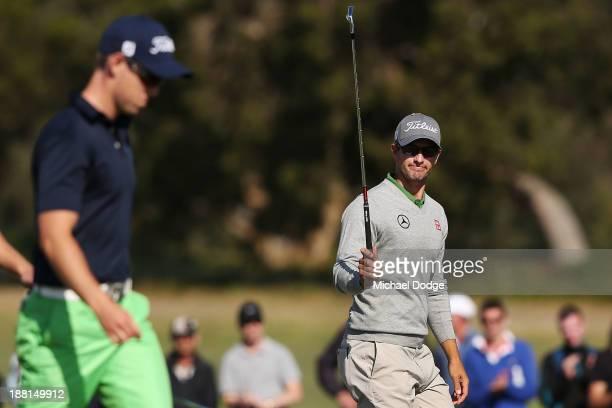 Adam Scott of Australia waves to the crowd next to Nathan Holman of Australia on the 18th hole during round three of the 2013 Australian Masters at...
