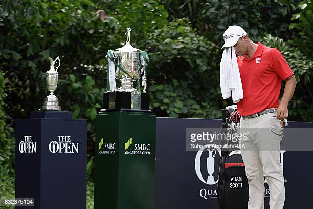 Adam Scott of Australia wipes off his sweat before teeing off on the first hole next to the SMBC Singapore Open trophy and the Claret Jug during day...