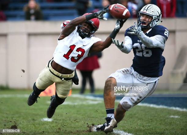Adam Scott of the Harvard Crimson reaches for a pass while under pressure from Tobe Ezeokoli of the Yale Bulldogs in the second half of a game at the...
