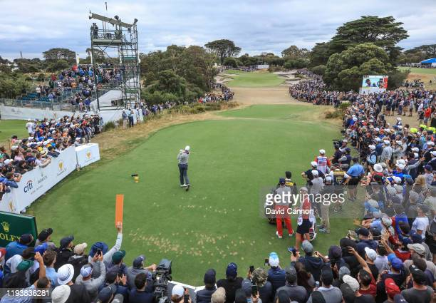 Adam Scott of the International Team plays his tee shot on the par 3 third hole in his match with Louis Oosthuizen in their match against Dustin...