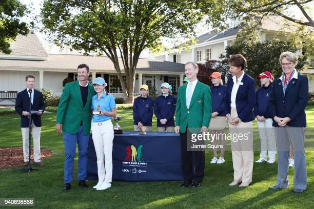 Adam Scott presents Jackie Feldman participant in the 1415 girls with her trophy during the Drive Chip and Putt Championship at Augusta National Golf...