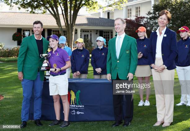 Adam Scott presents Jami Morris participant in the 1415 girls with her trophy during the Drive Chip and Putt Championship at Augusta National Golf...