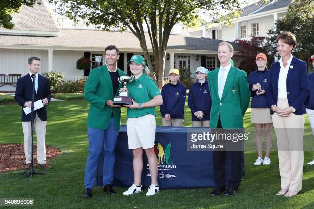 Adam Scott presents Katherine Schuster participant in the 1415 girls with her trophy during the Drive Chip and Putt Championship at Augusta National...