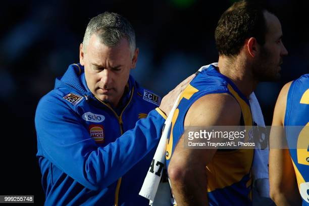 Adam Simpson Senior Coach of the Eagles pats Shannon Hurn on the back during the round 17 AFL match between the Collingwood Magpies and the West...
