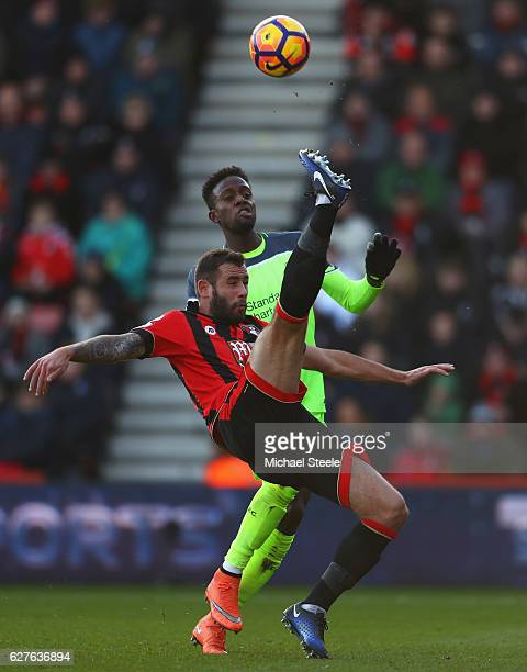 Adam Smith of AFC Bournemouth clears from Divock Origi of Liverpool during the Premier League match between AFC Bournemouth and Liverpool at Vitality...