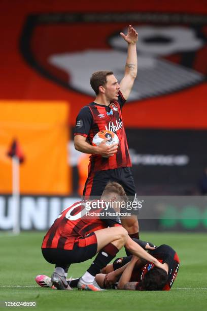 Adam Smith of AFC Bournemouth goes down injured as David Brooks checks on him and Dan Gosling calls for the medical team during the Premier League...