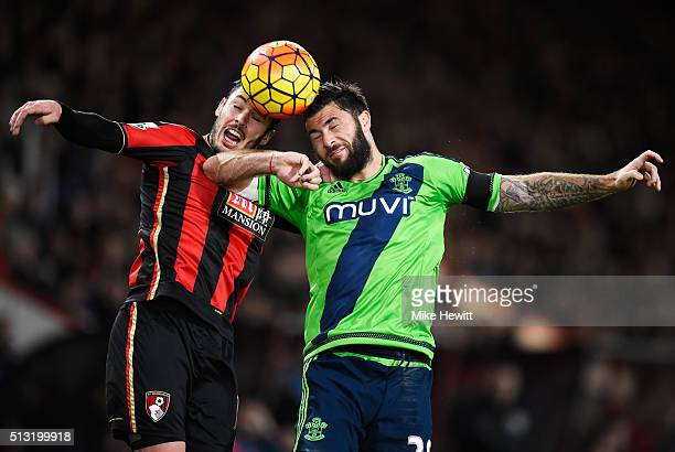 Adam Smith of Bournemouth and Charlie Austin of Southampton compete for the ball during the Barclays Premier League match between AFC Bournemouth and...
