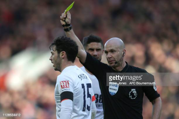 Adam Smith of Bournemouth is booked by referee Anthony Taylor during the Premier League match between Liverpool FC and AFC Bournemouth at Anfield on...