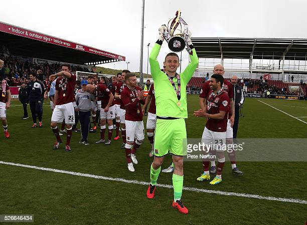 Adam Smith of Northampton Town celebrates with the Sky Bet League Two champions trophy after the Sky Bet League Two match between Northampton Town...